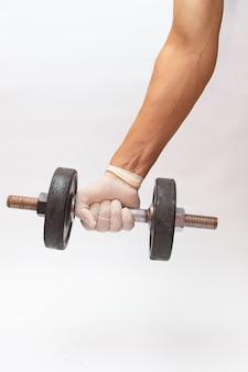 Gros plan d'une main dans un gant médical tenant un outil de musculation pendant la pandémie de covid-19