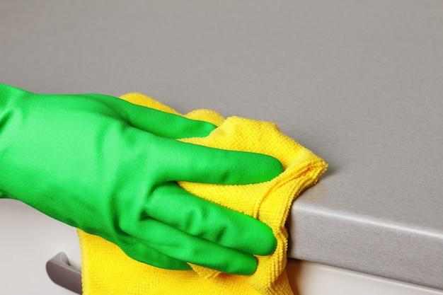 Gros plan d'une main dans un gant de protection tenant une serviette et essuyant un comptoir.