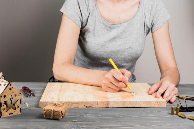Gros plan de la main, dessinant sur une planche de bois dure pour la fabrication artisanale