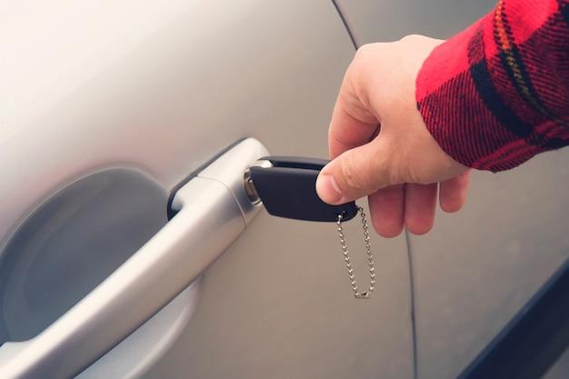 Gros plan de la main droite masculine tournant la clé dans le trou de la porte de la voiture. l'homme utilise la clé pour ouvrir le nouveau véhicule. location de voitures. obtenir le permis de conduire. se préparer à conduire. déverrouillage mécanique.