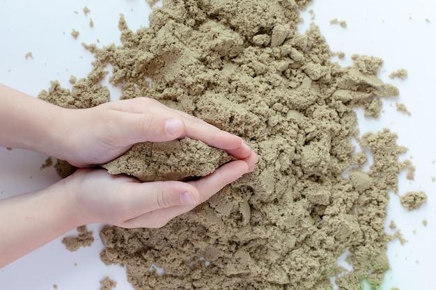 Gros plan de la main du bébé, jouant avec un sable cinétique