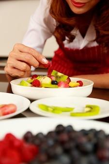 Gros plan de la main du chef mettant la framboise dans une délicieuse salade de fruits mélangés sucrés dans un bol blanc sur la table de la cuisine. concept d'aliments biologiques et naturels.