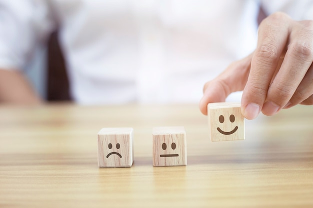 Gros plan sur la main du client, choisissez le visage souriant et le visage triste flou sur un cube en bois