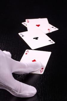 Gros plan de la main du croupier en gants blancs dans un casino distribuant des cartes sur une table sombre