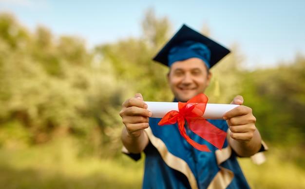 Gros plan sur la main du diplômé levant les mains et célébrant avec un certificat en mains et se sentant tellement heureux le jour du début, concept de réussite de l'éducation