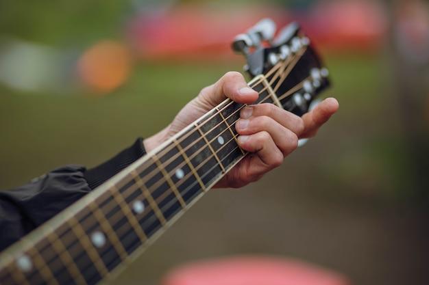 Gros plan de la main du guitariste jouant de la guitare acoustique.