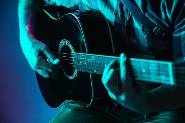 Gros plan de la main du guitariste jouant de la guitare, copyspace, macro shot