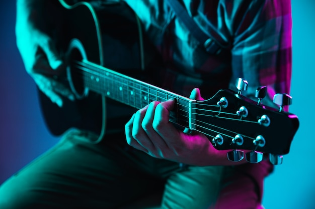 Gros plan de la main du guitariste jouant de la guitare, macro. concept de publicité, passe-temps, musique, festival, divertissement. personne improvisant inspirée. copyspace pour insérer une image ou du texte. néon coloré éclairé.