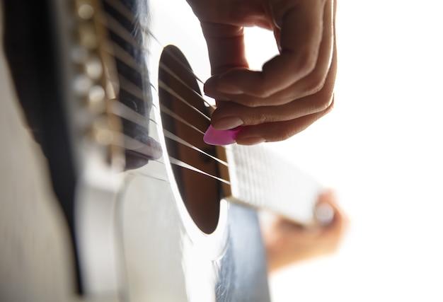 Gros plan de la main du guitariste jouant de la guitare macro shot concept de musique de passe-temps publicitaire