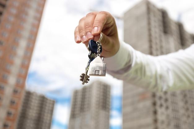 Gros plan de la main du jeune homme d'affaires tenant les clés de la nouvelle maison