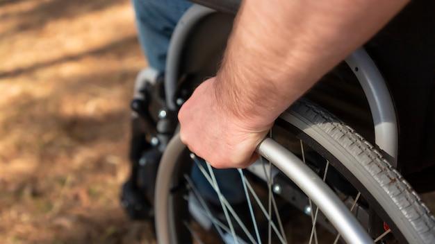 Gros plan sur la main du jeune homme au volant du fauteuil roulant vue latérale