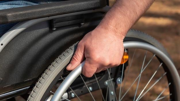 Gros plan sur la main du jeune homme au volant du fauteuil roulant
