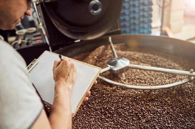 Gros plan de la main du jeune homme écrivant sur le presse-papiers tandis que monsieur debout par le plateau de refroidissement avec des grains de café torréfiés