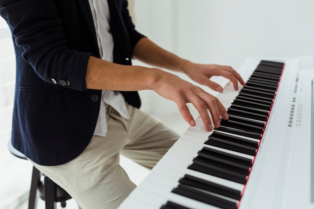 Gros plan de la main du jeune homme jouant du piano