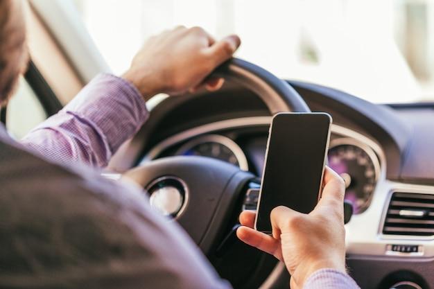 Gros plan de la main du jeune homme avec une voiture de conduite de smartphone