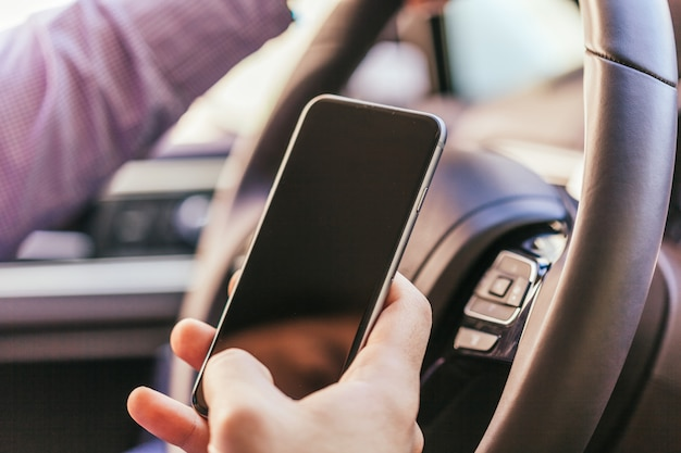 Gros plan de la main du jeune homme avec la voiture conduite smartphone