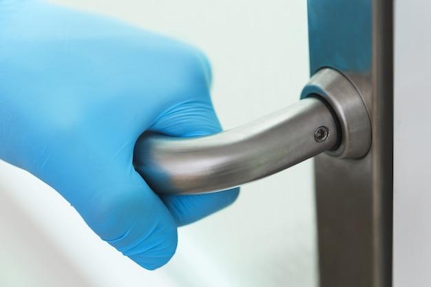 Gros plan de la main du médecin sur la poignée de porte en métal