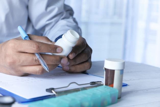 Gros plan de la main du médecin tenant le récipient de la pilule.