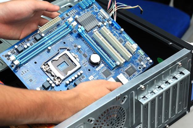 Gros plan sur la main du technicien assemblant l'ordinateur personnel