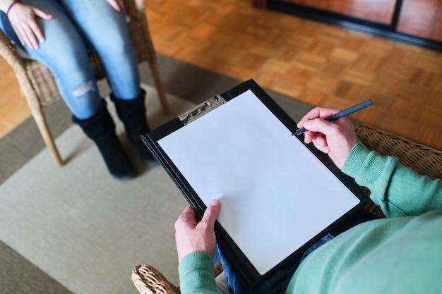 Gros plan de la main du thérapeute écrit des notes lors d'une séance de conseil avec une seule femme assise sur un canapé