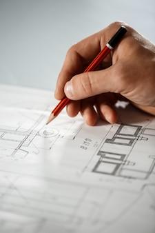 Gros plan de la main du travailleur sur le dessin.