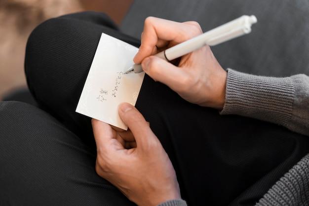 Gros plan main écrit une note