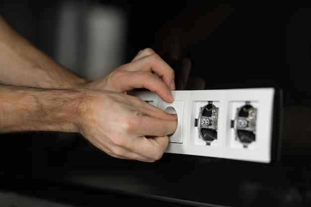 Gros plan de la main d'un électricien démontant une prise électrique blanche