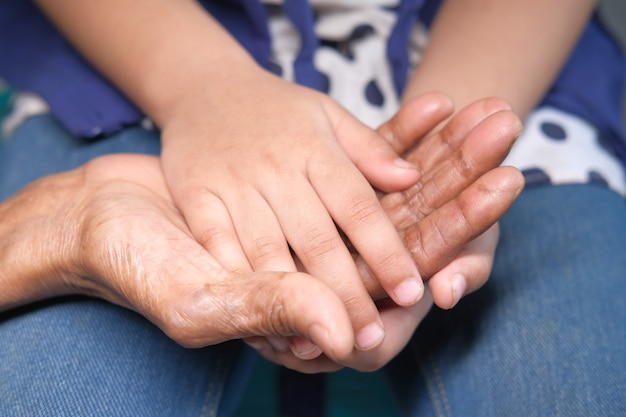 Gros plan de la main de l'enfant tenant la main des femmes seniors
