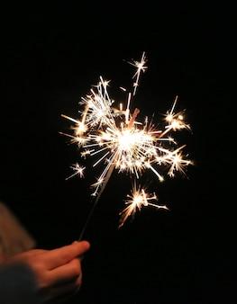 Gros plan, main enfant, tenue, flammes étincelantes sur l'obscurité au festival