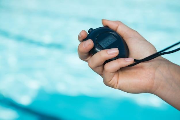 Gros plan de la main de l'entraîneur tenant le chronomètre au bord de la piscine