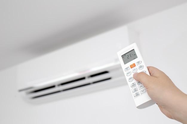 Gros plan d'une main féminine actionnant une télécommande d'un climatiseur domestique