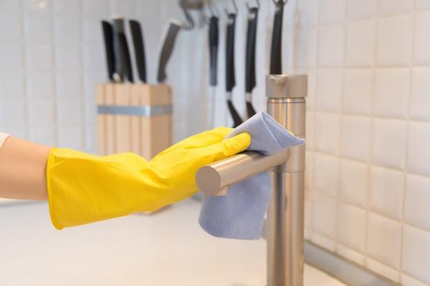 Gros plan de la main féminine dans les gants de nettoyage du robinet de cuisine