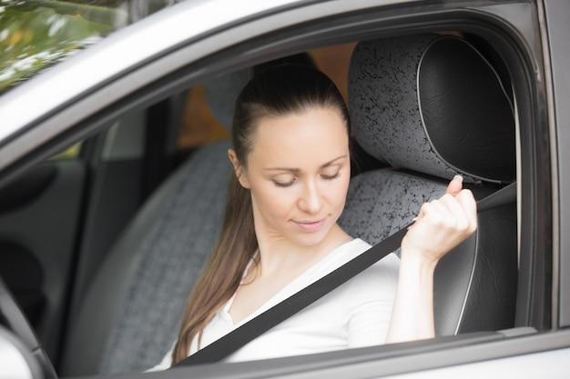 Gros plan de la main féminine fixant une ceinture de sécurité