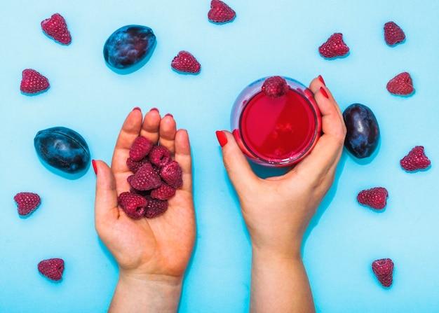 Gros plan, main féminine, jus, prunes, framboises, fond bleu