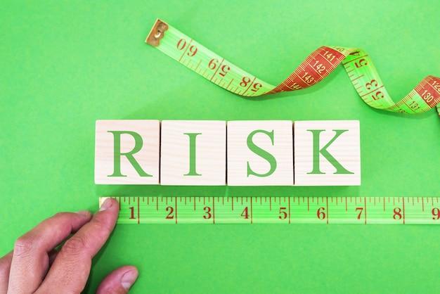 Gros plan sur une main féminine mesurant des cubes avec le mot risque à l'aide d'un ruban à mesurer vert sur fond vert.