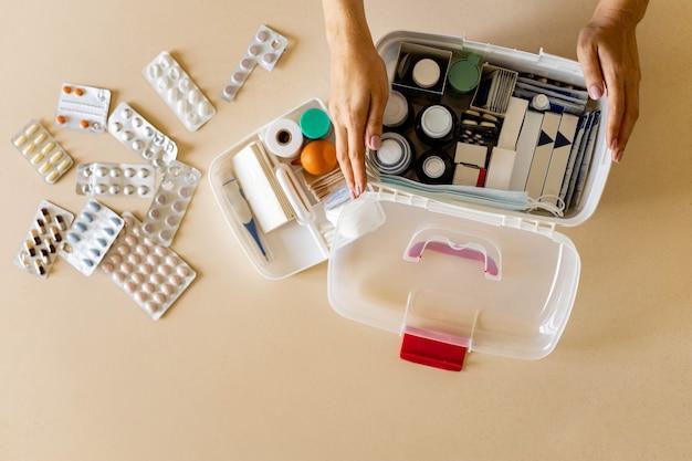 Gros plan de la main féminine plaçant l'approvisionnement d'urgence de l'organisation de stockage de la trousse de premiers soins domestique de médicament