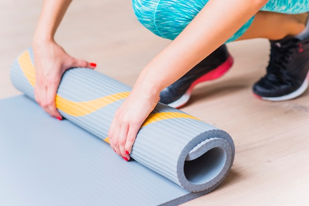 Gros plan, main féminine, plier, yoga, tapis