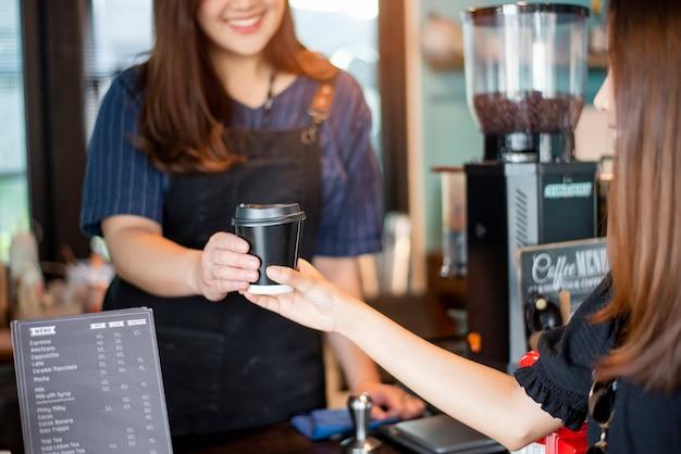 Gros plan d'une main féminine prend un café chaud de barista
