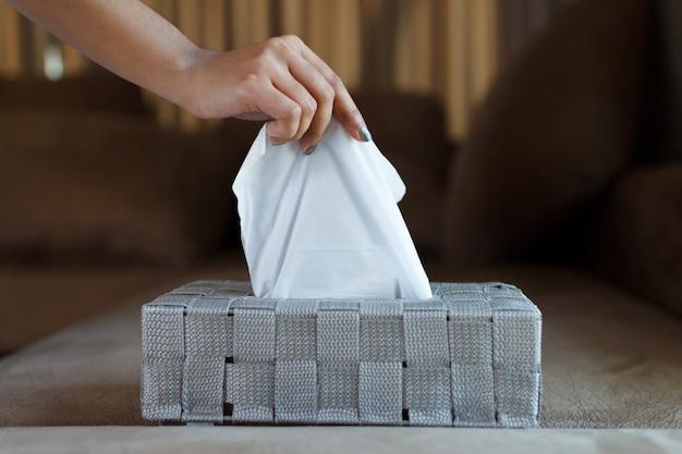 Gros plan d'une main féminine ramassant un papier de soie blanc dans une boîte grise.