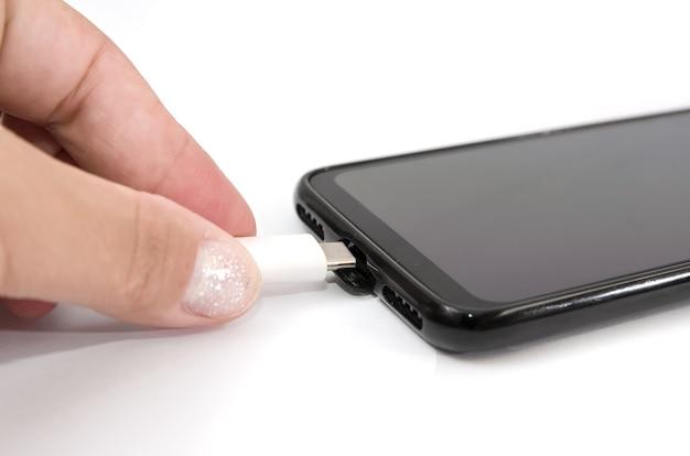 Gros plan de la main féminine reliant le câble de charge au smartphone isolé sur fond blanc