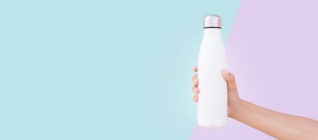 Gros plan d'une main féminine tenant une bouteille d'eau thermo en acier réutilisable blanche isolée sur deux fond de couleurs bleu et violet. vue panoramique de la bannière avec espace de copie.