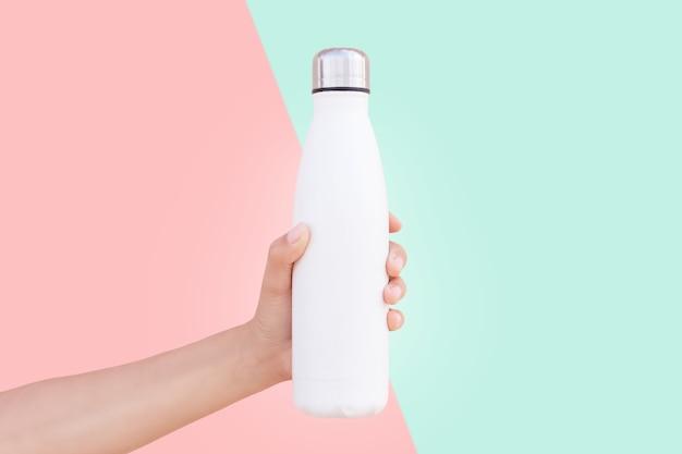 Gros plan d'une main féminine tenant une bouteille d'eau thermo en acier réutilisable blanche isolée sur deux fond de couleurs rouge et verte.