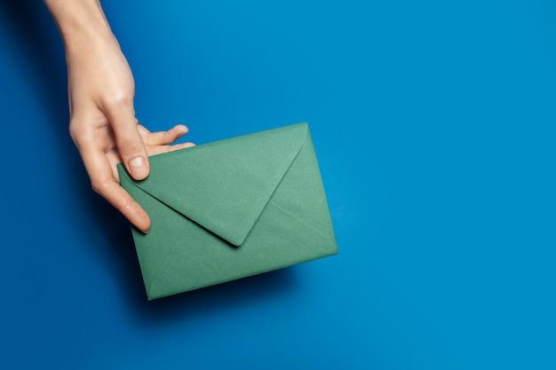 Gros plan d'une main féminine tenant une enveloppe de papier vert sur de couleur bleue.