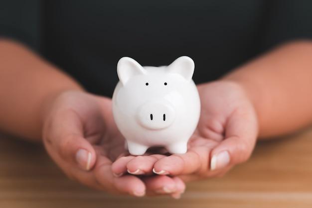 Gros plan de la main féminine tenant la tirelire économisez de l'argent et des investissements financiers