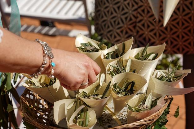 Gros plan d'une main féminine touchant les petits bouquets de fleurs de mariage
