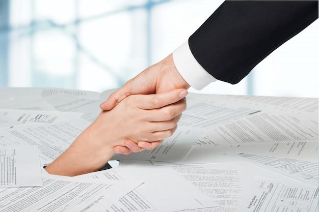 Gros plan sur une main de femme d'affaires dans une pile de papiers