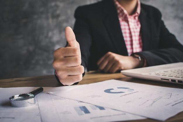 Gros plan main de femme d'affaires pouce en haut avec confiance sur fond de bureau