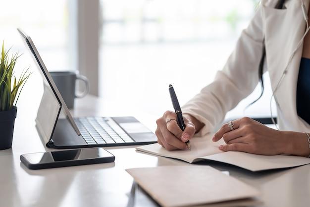 Gros plan d'une main de femme d'affaires tenant un stylo prenant des notes avec une tablette et un smartphone au bureau.