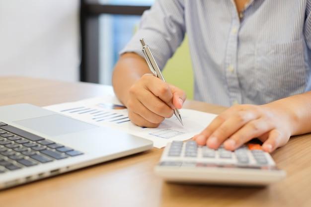 Gros plan sur la main de la femme en appuyant sur la calculatrice pour calculer l'estimation des coûts