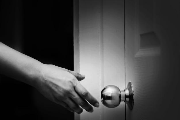 Gros plan de la main de la femme atteignant le bouton de la porte, ouvrant la porte dans un ton blanc